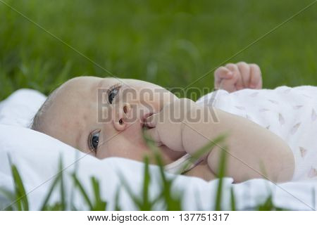 newborn baby lies on grass in park with hand in mouth
