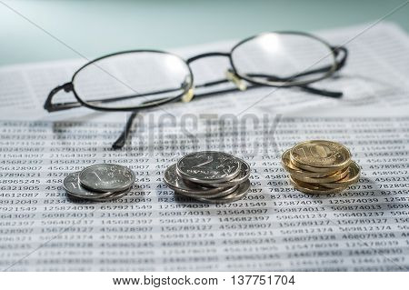 Workplace with coins documents and glasses. Account money.