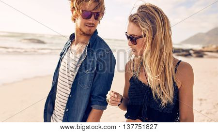 Closeup portrait of young couple talking while walking along a beach. Young man and woman strolling on a beach.