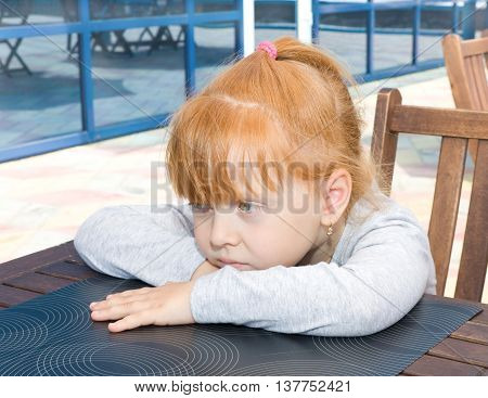 Sad child sitting at a table in a cafe