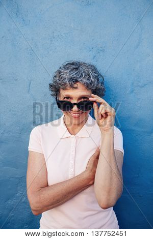 Vertical portrait of attractive senior woman peeking over sunglasses against blue wall. Middle aged female looking at camera and smiling.