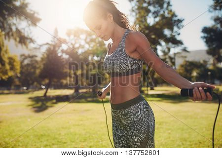 Woman Exercising With Skipping Rope Outdoors