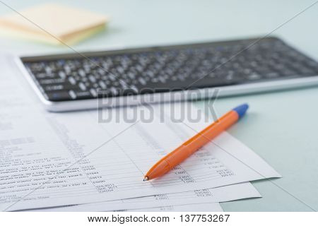Workplace Accountant. Documents, Pen, Keyboard, Paper For Notes. On Paper, The Table Is A List Of Pr