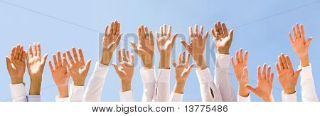 Close-up of several human hands raised against cloudy sky