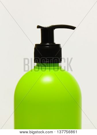 Half of green bottle with black dispenser
