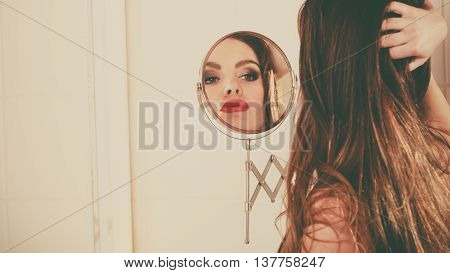 Young Girl Looking Into A Mirror.
