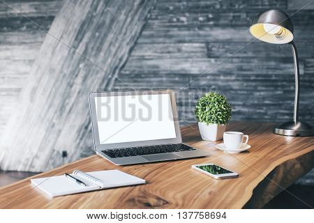 Wooden designer desktop with blank white laptop stationery items coffee cup cell phone plant and table lamp. Mock up