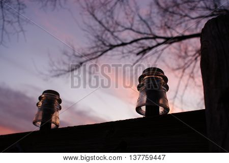 Old clear glass telephone insulators on pole at sunset