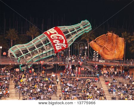 Fans Sitting In Bleacher Section With Large Glove And Giant Coca-cola Slide Being Enjoyed On The Sec