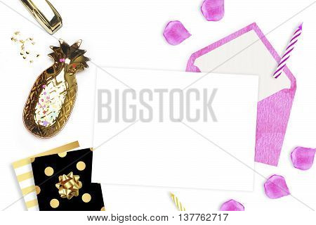 White background with an invitation envelope. Gold woman items on table.Top view glamour style. Flat lay party desk. Table view workspace. Pineapple. Polka pattern