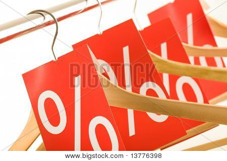 Close-up of several wooden hangers with red labels showing discount on them