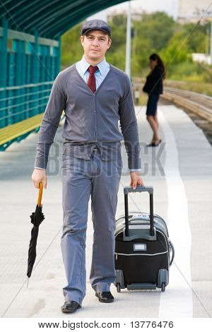 Handsome man walking down railway station with umbrella and baggage