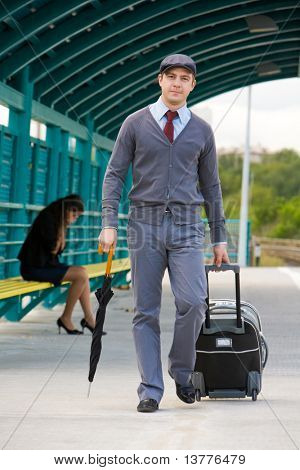 Handsome man walking down railway station with umbrella and baggage with sad girl on background