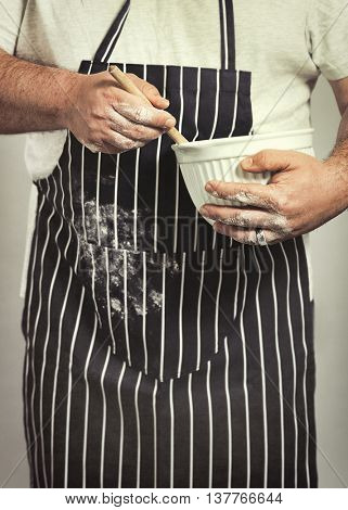 Baker in apron covered with flour holding mixing bowl