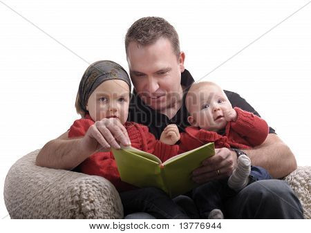 Father Reading A Story At His Little Daughters
