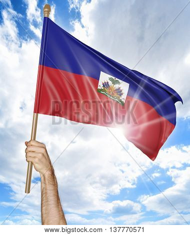Person's hand holding the Haitian national flag and waving it in the sky, 3D rendering
