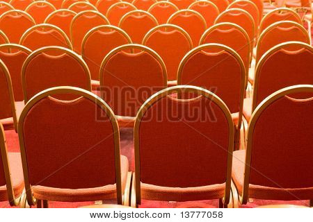 Image of several rows of red armchairs in conference hall