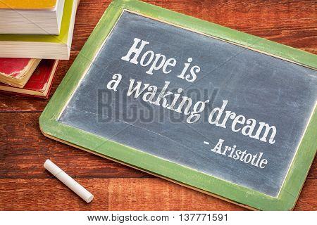 Hope is a waking dream - Aristotle quote - text on a slate blackboard with a white chalk and a stack of books against rustic wooden table