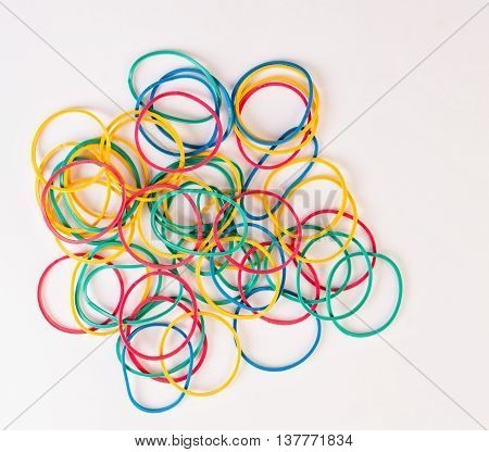 pile of rubber bands of different colors on white