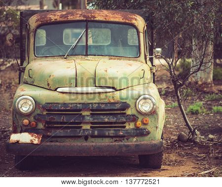 Adelaide Australia - January 11 2015: Old rusty abandoned pickup truck parked in the forest. Color-toning applied