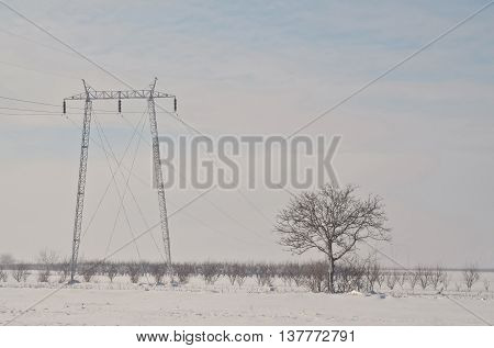 High voltage electric pole in gloomy winter day