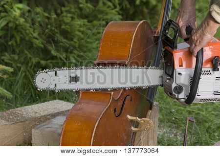 Hands with a chainsaw about to destroy a cello concept of no more music