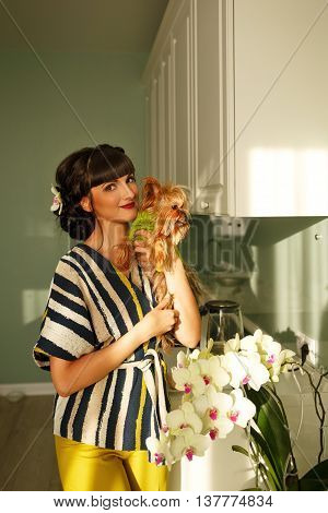 Girl holds a Yorkshire terrier. Pedigree dog. Funny animals. Girl and pet in kitchen