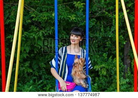 Girl hugging Yorkshire Terrier. Pedigree dog. Funny animals. Girl and pet ride on a swing
