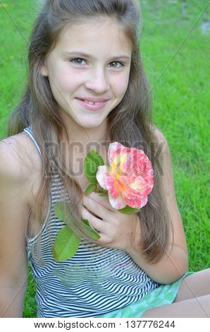 The young girl on nature with a bouquet of pale pink roses