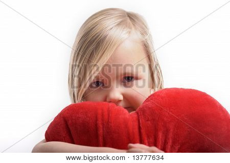 Little Girl Holding A Heart Shaped Pillow