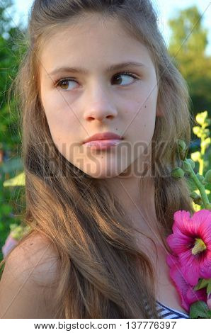 Young girl with her hair next to mallow