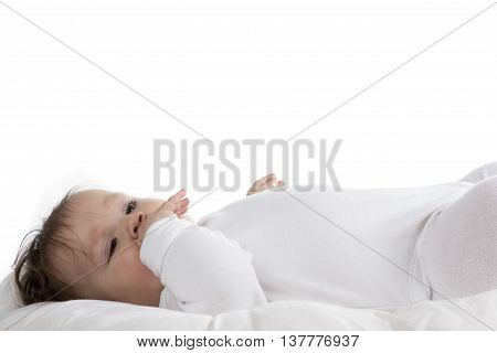 teething baby with hand in mouth isolated on white background