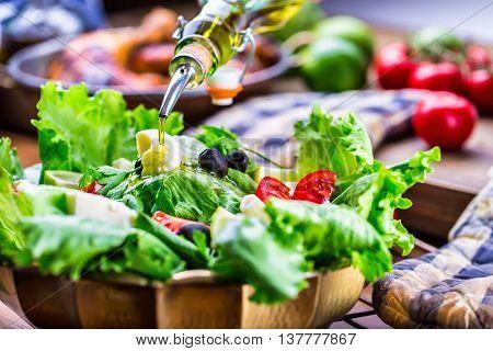 Vegetable lettuce salad. Olive oil pouring into bowl of salad. Italian Mediterranean or Greek cuisine. Vegetarian vegan food.