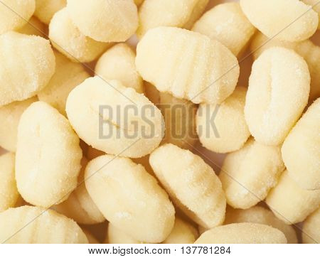 Surface covered with multiple gnocchi dough dumplings as a close-up backdrop composition