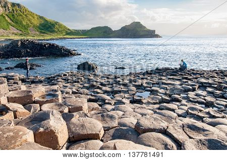 NORTHERN IRELAND UK - AUGUST 3, 2016: Tourists taking photos on Giants Causeway unique geological hexagonal formations of volcanic basalt rocks on the coast in Northern Ireland UK