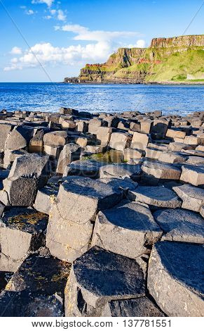Giants Causeway unique geological hexagonal formations of volcanic basalt rocks and cliffs on Atlantic coast in County Antrim Northern Ireland in sunset light. UNESCO World heritage site