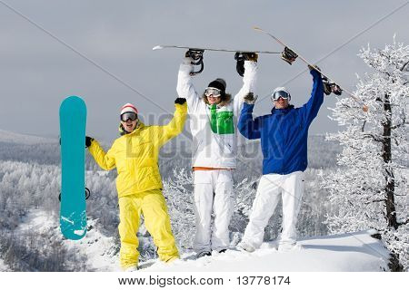 Portrait of three happy young men with snowboards raising their arms