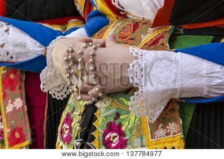 CAGLIARI, ITALY - May 1, 2015: 359 ^ Religious Procession of Sant'Efisio - Sardinia - particularly of the hands of a girl in traditional Sardinian costume