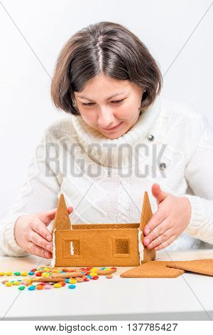 Girl In A White Sweater Making A Gingerbread House