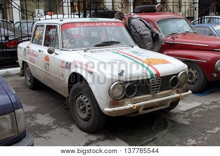 PERM RUSSIA - JUNE 29 2016: Rally of retro-cars Peking-Paris 2016 June 29 2016 in Perm Russia. White Alfa Romeo Giulia Super is in the city after the next stage.