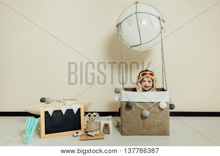 Happy child playing in basket of air balloon. Kid having fun at home. Young pilot indoors at solid color background with copy space. Boy in hat like a helmet looking at camera. Blank chalkboard.