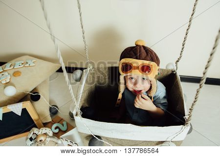 Happy boy playing in handmade basket of air balloon. Child having fun at home. Young pilot indoors at beige background. Kid in hat like a helmet looking at camera. Blank chalkboard