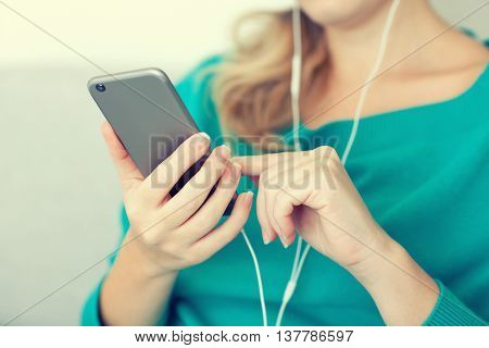 Woman holding phone and listening to music on headphones