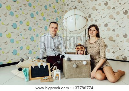 Portrait of happy kid with parents at home on background of air balloon and blank chalkboard with copy space. Child having fun at home. Looking at camera