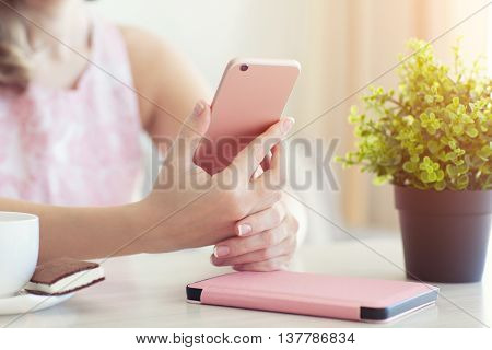 woman in summer cafe with a cup of coffee holding pink phone