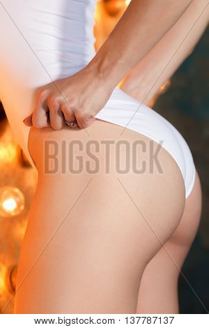 Young sportive woman with beautiful bottoms and slim waistline touching her bodysuit. Fitness and healthy lifestyle concept