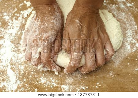 female hands in a flour knead dough on wooden board