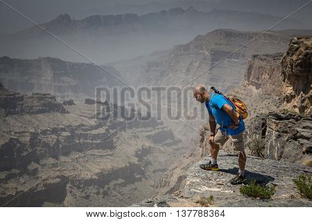 JEBEL SHAMS, OMAN - CIRCA AUGUST, 1015: a hiker is looking over an open ledge into a canyon on the way up the highest peak in Oman called Jebel Shams