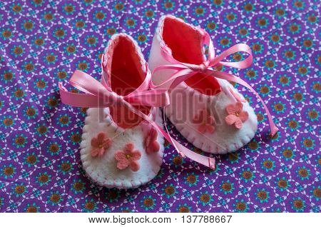 Newborn baby girl pink booties in bed