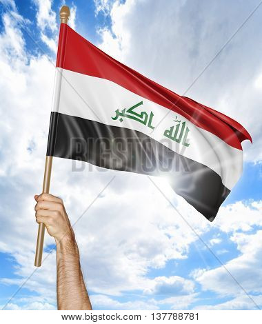 Person's hand holding the Iraqi national flag and waving it in the sky, 3D rendering